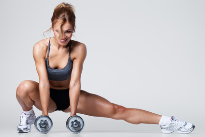 Smiling athletic woman pumping up muscles with dumbbells and stretching legs
